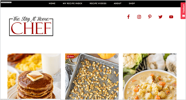 This is a screenshot of The Stay At Home Chef Website. At the top is a black bar with the following navigation options: Home, My Recipe Index, Recipe Videos, About, Shop. The Stay AT Home Chef title appears in the upper left in a script style font. Red social icons for Facebook, Instagram, Pinterest, Twitter, and YouTube appear in the upper right. Below the header are three photos from left to right: a stack of pancakes with a pat of butter on top, a pan of roasted pumpkin seeds, a bowl of cauliflower soup. Rachel Farnsworth started this site as a blog when she became a stay-at-home mom.